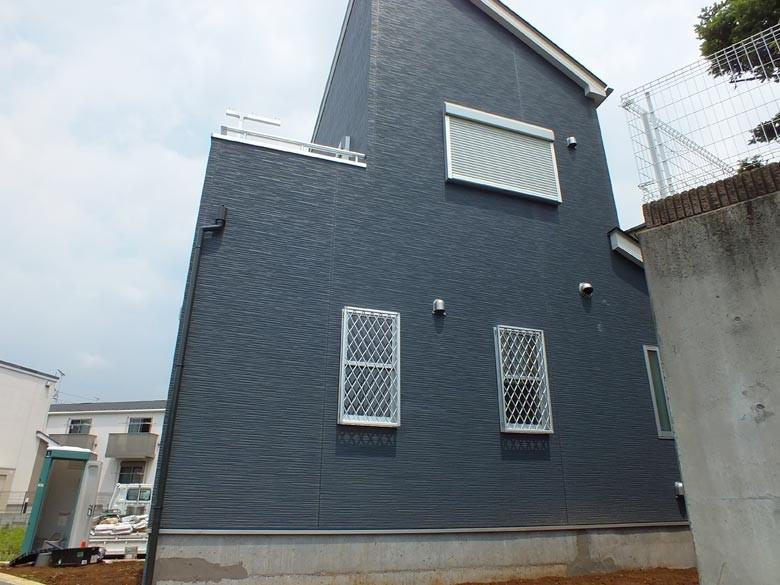 壁は濃い目のブルーのサイディング、サッシはシルバー色です