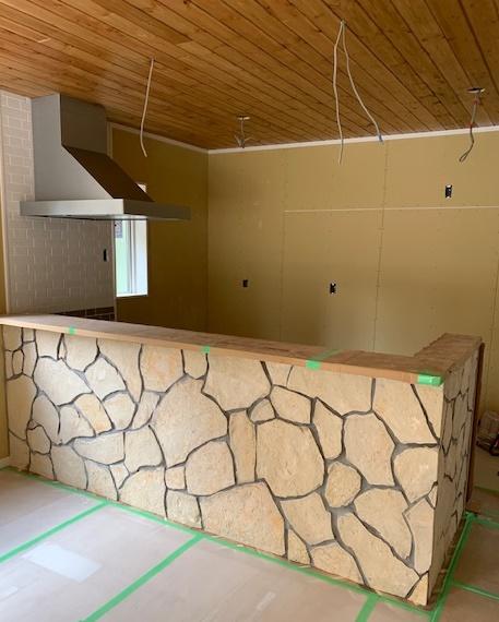 対面キッチンの壁には乱形石を貼りワイルドに!